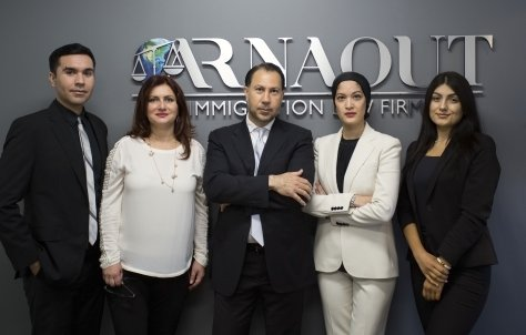 The lawyers at Arnaout Immigration Law Firm standing in front of their signage at their office.